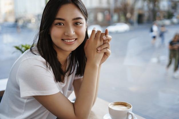 Portret van mooie natuurlijke vrouw koffie drinken in café alleen, zittend in de buurt van raam, glimlachend op camera gelukkig.
