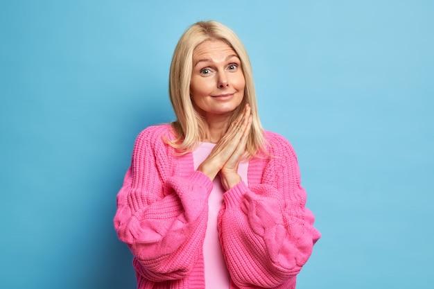 Portret van mooie oma houdt handpalmen tegen elkaar gedrukt en ziet er merkwaardig gekleed in gebreide roze trui geniet van het leven bij pensionering.