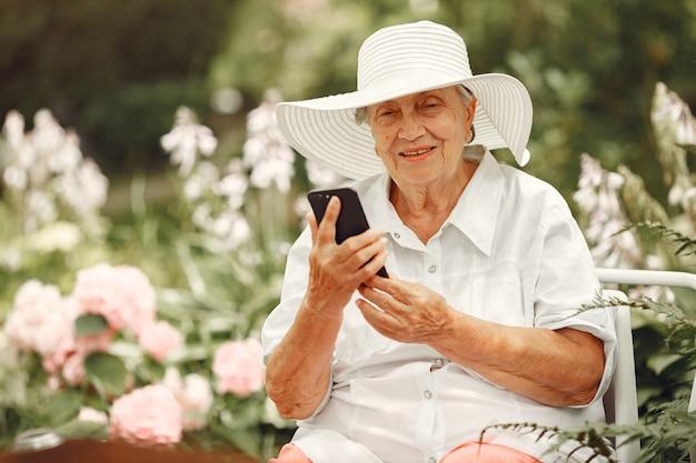 Portret van mooie oude vrouw in het park. oma in een witte hoed. hogere vrouw met mobiele telefoon.