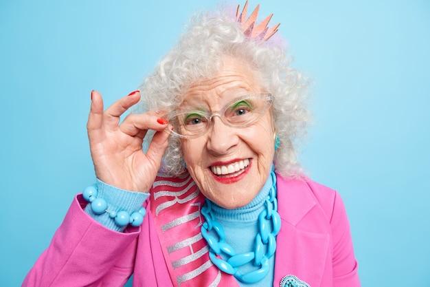 Portret van mooie oudere grijsharige vrouw houdt hand op de rand van de bril en glimlacht vrolijk