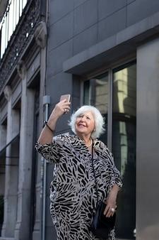 Portret van mooie oudere vrouw met wit haar op straat die een foto maakt
