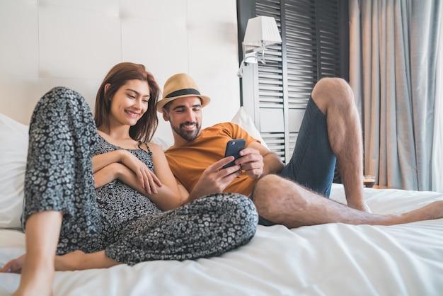 Portret van mooie paar ontspannen en met behulp van mobiele telefoon terwijl tot op bed in hotelkamer. levensstijl en reisconcept.