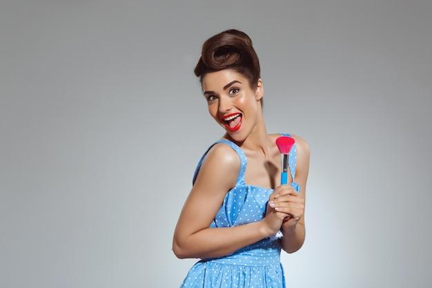 Portret van mooie pin-up vrouw bij studio met make-up borstel