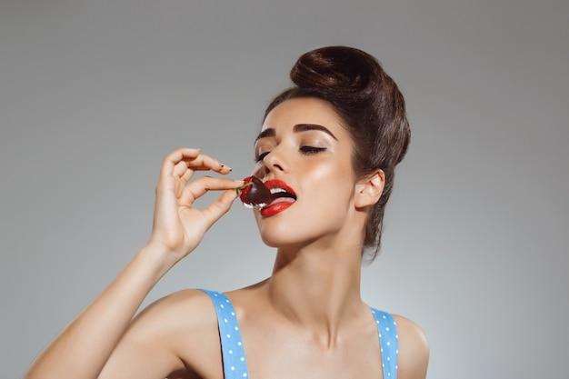 Portret van mooie pin-up vrouw die aardbei in chocolade eet