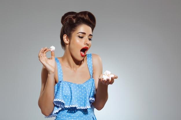 Portret van mooie pin-up vrouw met snoepjes in handen