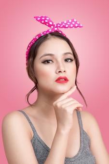 Portret van mooie pinup aziatische vrouw met vintage make-up en kapsel. geïsoleerd op roze achtergrond