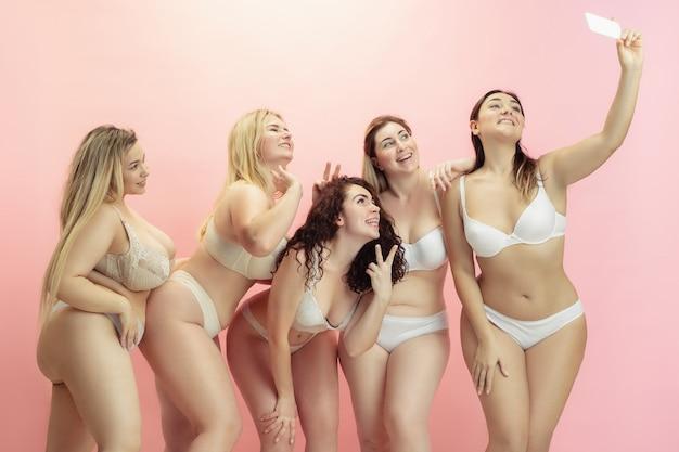 Portret van mooie plus grootte jonge vrouwen die op roze stellen