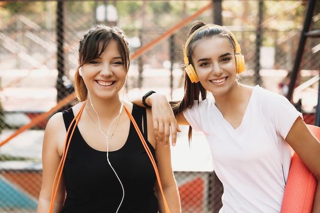 Portret van mooie plus grootte vrouw die camera bekijkt die lacht terwijl alvorens te doen afvallen oefening met haar vrouwelijke vriend die haar helpt.