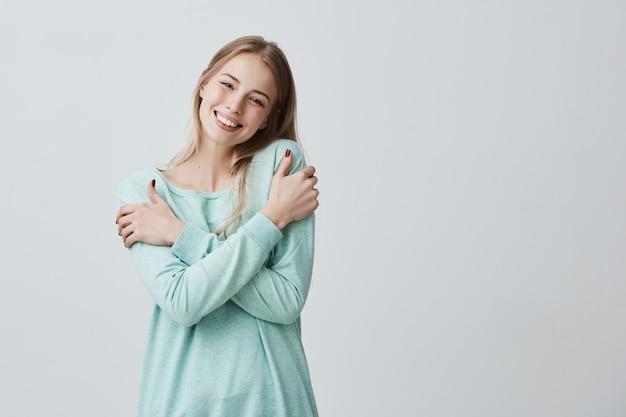 Portret van mooie positieve jonge europese vrouw met charmante glimlach en lang blond haar genieten van zachte stof van haar nieuwe lichtblauwe trui poseren