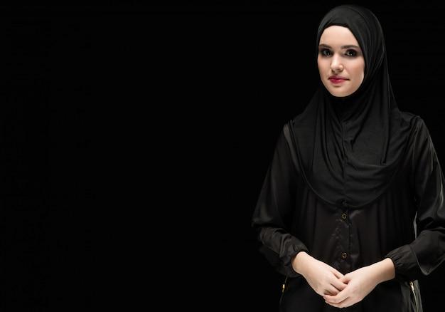Portret van mooie positieve jonge moslimvrouw die zwarte hijab draagt
