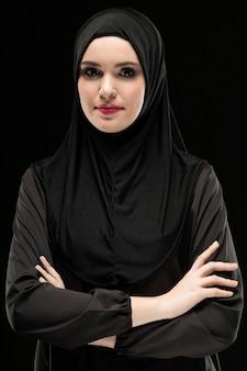 Portret van mooie positieve jonge moslimvrouw die zwarte hijab dragen als conservatief manierconcept met gekruiste wapens die op zwarte achtergrond glimlachen