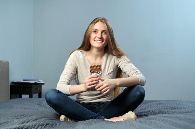 Portret van mooie positieve jonge vrouw met chocolade met hazelnoten,