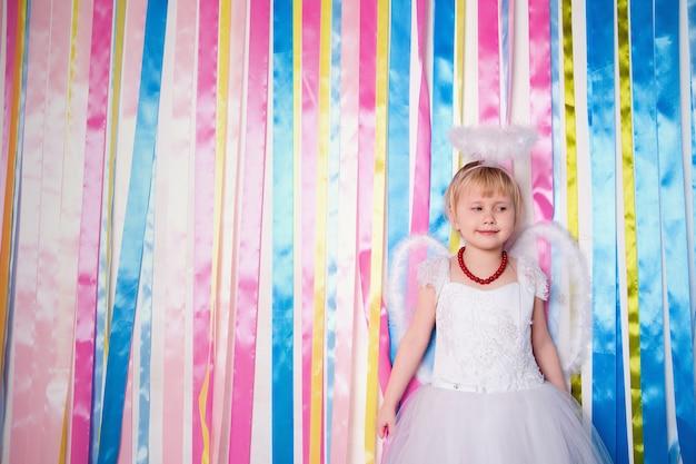 Portret van mooie prinses meisje in witte jurk met witte nimbus en vleugels