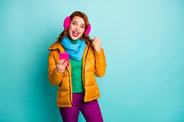 Portret van mooie reis dame houden telefoon vieren prestatie eerste online geld inkomen dragen trendy casual gele overjas sjaal paarse broek.