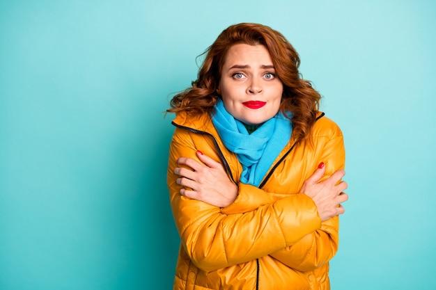Portret van mooie reiziger dame ijzige winterdag schudden lichaam lopen straat knuffel zichzelf dragen trendy casual gele overjas blauwe sjaal.