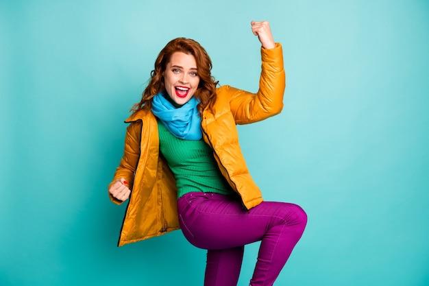 Portret van mooie reiziger dame vuisten goed humeur vieren succesvolle prestatie dragen trendy casual gele overjas sjaal violette broek.