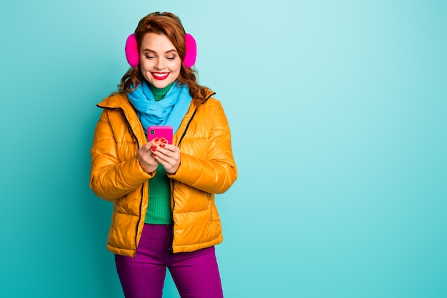 Portret van mooie reiziger dame wacht telefoon zoeken kijk kaart gebruiker navigatiesysteem draag trendy casual gele overjas sjaal paarse broek.