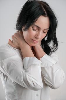 Portret van mooie rijpe donkerbruine vrouw die op grijze witte achtergrond, exemplaarruimte wordt geïsoleerd