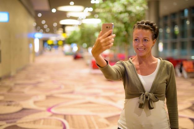Portret van mooie rijpe toeristenvrouw die van het leven genieten tijdens het reizen in de stad van singapore