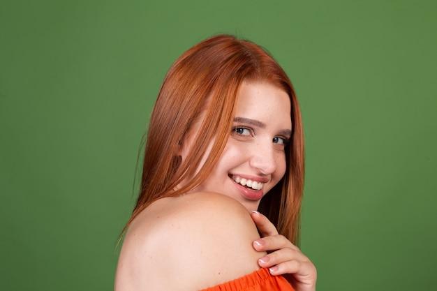 Portret van mooie rode haar jonge vrouw met gladde natuurlijke zachte huid met blote schouders op groene muur, schoonheidsconcept