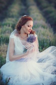 Portret van mooie romantische vrouw in fee gebied van lavendel met boeket
