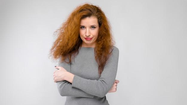 Portret van mooie roodharige ongelukkige jonge vrouw in grijze kleren op grijze achtergrond