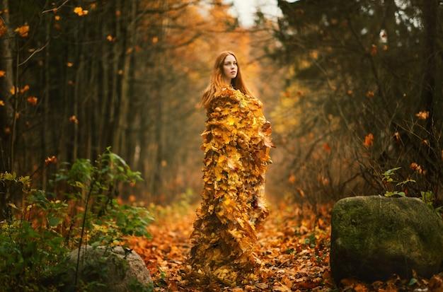 Portret van mooie roodharige vrouw, herfstbladeren jurk in het herfstpark