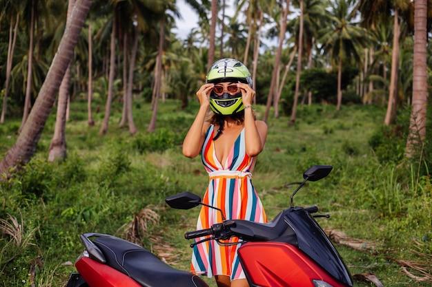 Portret van mooie ruiter vrouw in geelgroene motorhelm en kleurrijke lichte zomerjurk in de jungle op tropisch veld onder palmbomen.