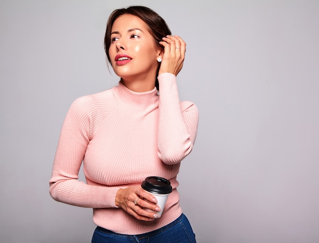 Portret van mooie schattige brunette vrouw model in casual zomer roze kleding zonder make-up geïsoleerd op grijs. koffie drinken