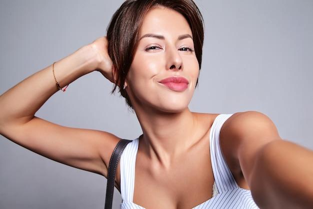 Portret van mooie schattige brunette vrouw model in casual zomerjurk zonder make-up maken selfie foto op telefoon geïsoleerd op grijs met handtas