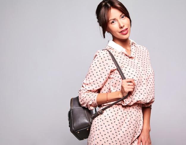 Portret van mooie schattige brunette vrouw model in casual zomerkleding zonder make-up geïsoleerd op grijze muur met handtas