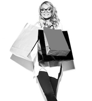 Portret van mooie schattige gelukkig lieve lachende blonde vrouw vrouw die in haar handen grote kleurrijke boodschappen tassen in hipster kleding op wit wordt geïsoleerd