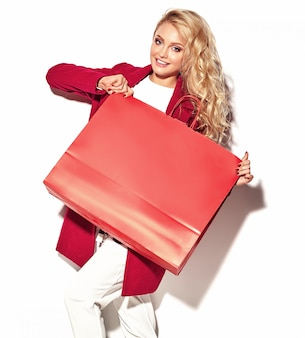 Portret van mooie schattige gelukkig zoete verrast blonde vrouw meisje bedrijf in haar handen grote boodschappentas in hipster rode kleding op wit wordt geïsoleerd