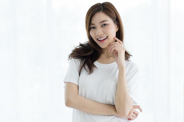 Portret van mooie schattige jonge aziatische vrouw lachend met een zelfverzekerde en gracieuze manier. ze steekt haar hand op om haar kin aan te raken met een vriendelijke pose op witte gordijnen.