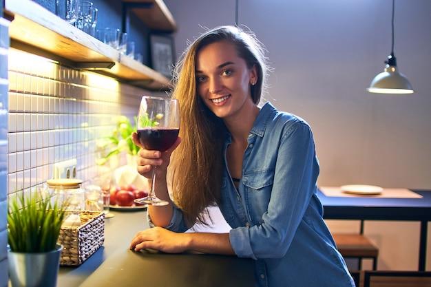 Portret van mooie schattige jonge casual lachende gelukkig drinkende vrouw met een glas rode wijn en zittend aan de tafel in de loft-stijl keuken thuis