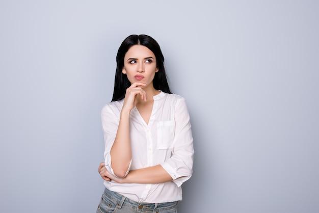 Portret van mooie schattige jonge vrouw met pruilende sensuele lippen en zwart haar fink over nieuw idee en iets te kijken