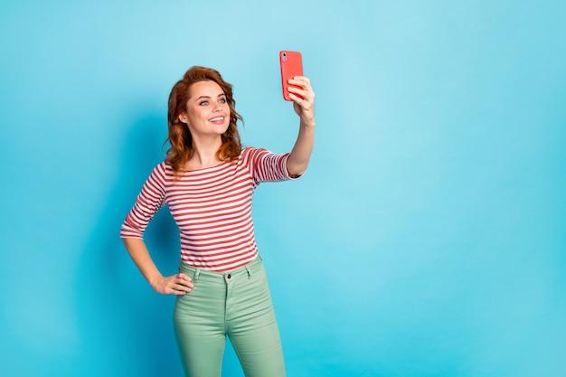 Portret van mooie schattige lieve vrouw genieten van de reis van de lentetijd maak selfie op mobiel dragen casual stijl trui geïsoleerd over blauwe kleur
