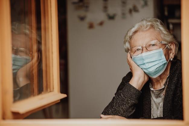 Portret van mooie senior vrouw of grootmoeder, gepensioneerde m / v kijken uit vanuit het raam