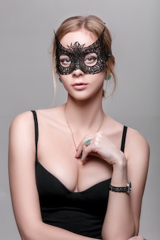 Portret van mooie sensuele blonde vrouw met groene ogen in zwart kantmasker op een donkere achtergrond. venetiaans masker