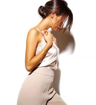 Portret van mooie sensuele brunette vrouw meisje in elegante witte klassieke kleding en wijde broek op witte achtergrond