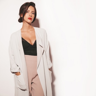Portret van mooie sensuele donkerbruine vrouw. meisje in elegante beige klassieke kleding en wijde broek. model geïsoleerd op wit
