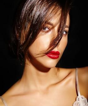 Portret van mooie sensuele schattige sexy brunette vrouw met rode lippen in pyjama's lingerie op zwarte achtergrond. met haar die haar haar bedekken