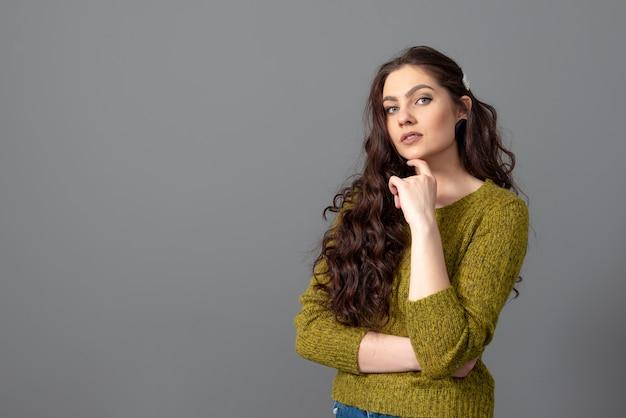 Portret van mooie sensuele vrouw met lang krullend haar tegen grijze ondergrond