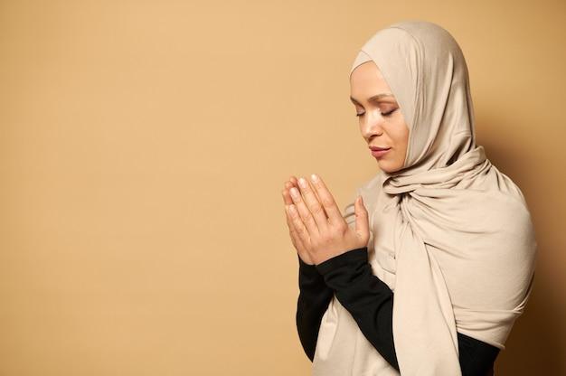 Portret van mooie serene moslimvrouw die beige hijab en traditionele kleding draagt die tijdens gebed namaz neerkijkt