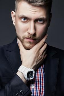 Portret van mooie sexy brutale mannen. blond met prachtig glanzend haar. een zakenman, een manager, een man in een overhemd. man met de klok aan de hand