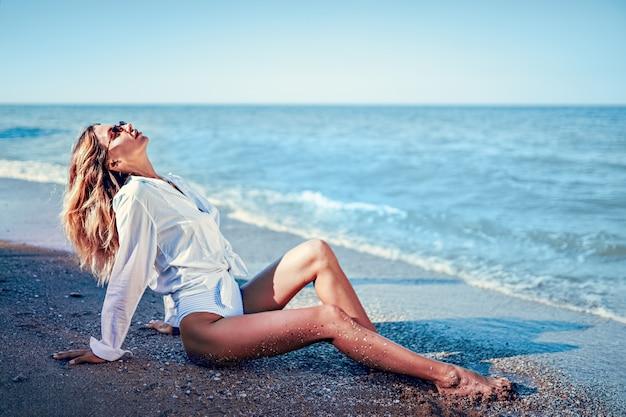 Portret van mooie sexy kaukasische sunbathed vrouw in zonnebril met lang haar in swimsuitand wit t-shirt liggend op zomer strand