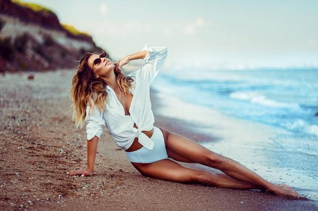 Portret van mooie sexy kaukasische zonnebaadde vrouw in zonnebril met lang haar in zwempak dat op de zomerstrand ligt