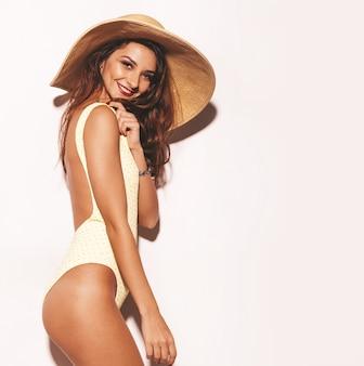 Portret van mooie sexy lachende brunette vrouw. meisje gekleed in casual zomer gele lichaam lingerie en grote hoed. model geïsoleerd