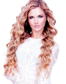 Portret van mooie sexy vrouw met lang blond krullend haar in witte jurk die zich voordeed op witte bakground.