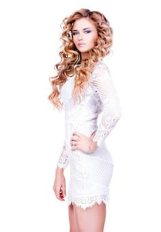 Portret van mooie sexy vrouw met lang blond krullend haar in witte jurk poseren over witte muur